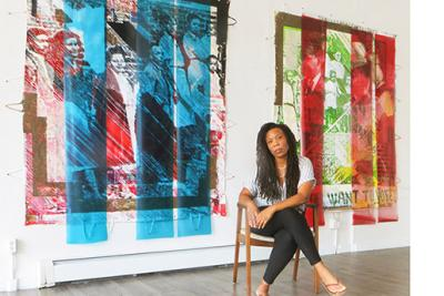 Tomashi Jackson seated in front of artwork